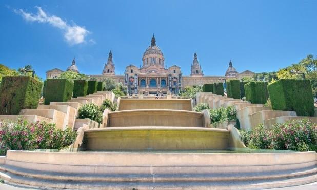 """Barcelona. Slot i Spanien, med store trapper ved siden, grønne hække og blomster. I midten et """"trappe"""" vandfald"""