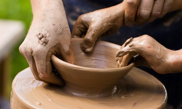 Keramik. Drejebænk, hvor 4 hænder er ved at dreje en skål.
