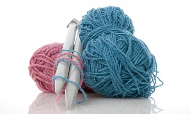 Garn. Lyserød og blå garnruller samt 2 strikkepinde